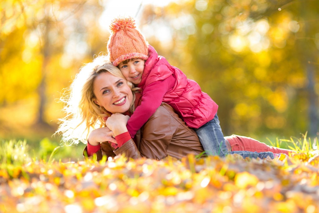 Parent and kid lying together on falling leaves. Happy family outdoor in autumn park. Smiling child is on mother's back.